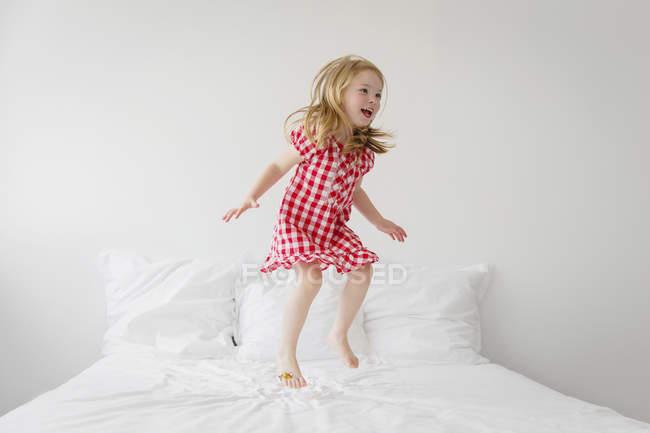 Jeune fille sautant sur le lit avec une couette blanche — Photo de stock