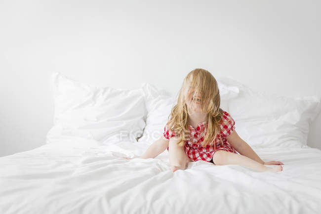 Jeune fille assise sur le lit — Photo de stock