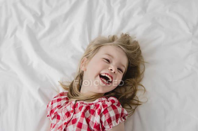 Garota de vestido xadrez, deitada na cama — Fotografia de Stock