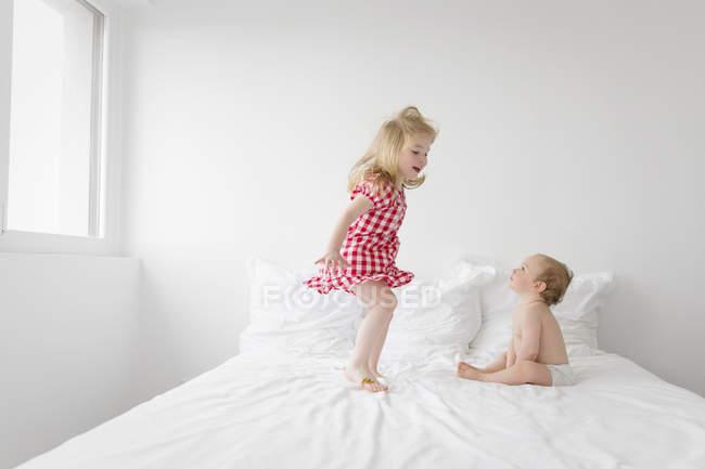 Jeune fille en robe damier sautant sur le lit — Photo de stock