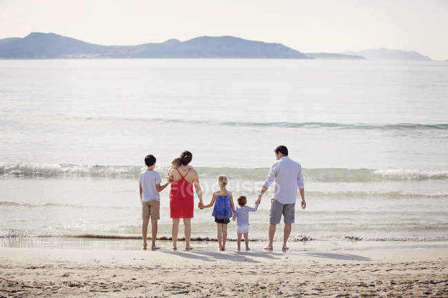 Man woman and children standing on beach — Stock Photo