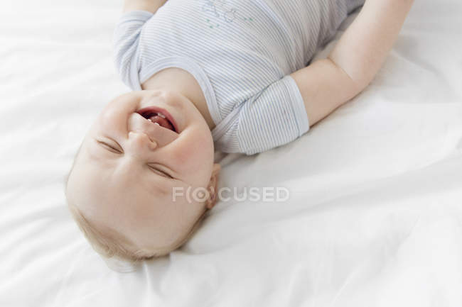 Baby boy with laughing with closed eyes — Stock Photo