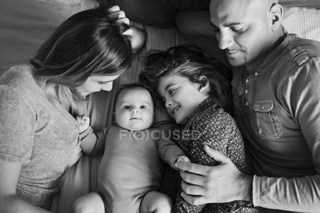 Family of four lying on bed. — Stock Photo