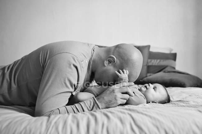 Mann umarmt Babymädchen auf Bett — Stockfoto