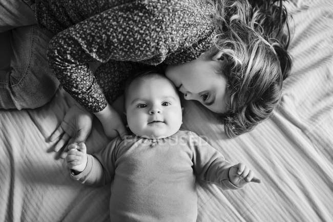 Girl and baby lying on bed — Stock Photo