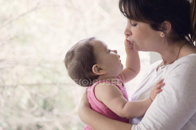 Baby girl touching mothers face — Stock Photo