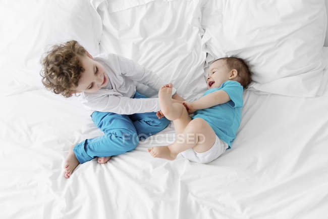 Little boy ticking baby on bed — Stock Photo