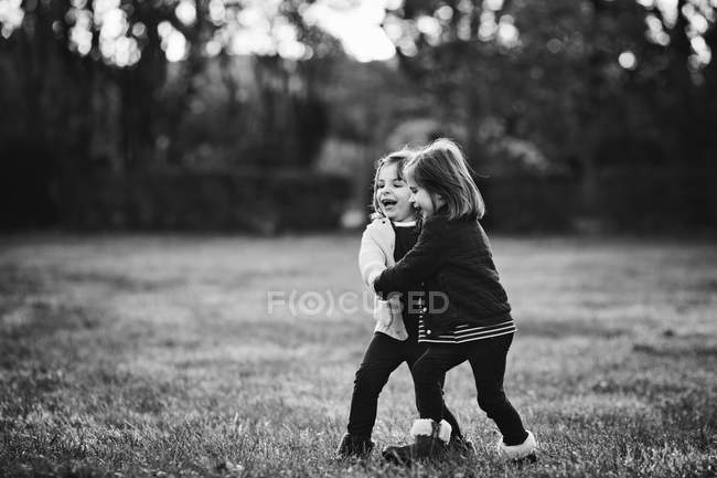 Sisters playing in park holding hands — Stock Photo