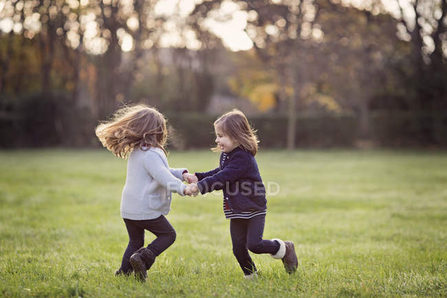 Sisters dancing in park holding hands — Stock Photo