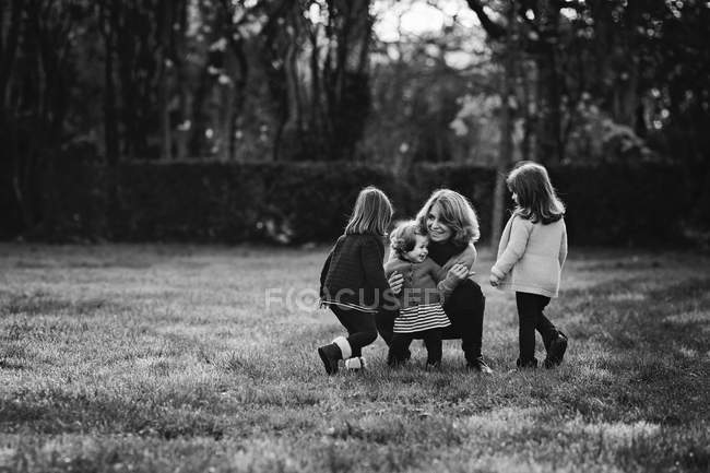 Mother hugging a toddler with two sisters — Stock Photo
