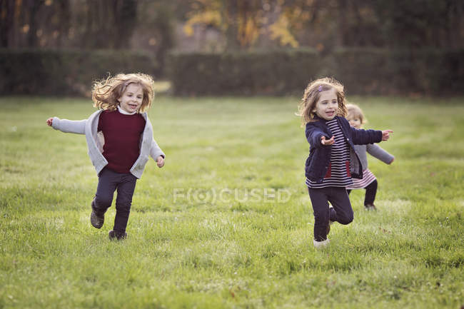 Young girls running across lawn — Stock Photo