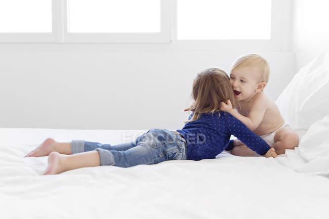 Baby boy hugging girl on bed — Stock Photo