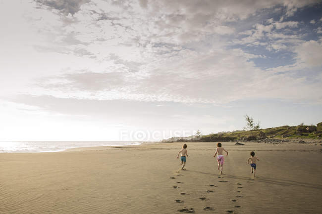 Three children running across beach. — Stock Photo