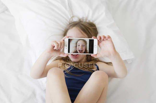 Mädchen auf Rücken hält smartphone — Stockfoto