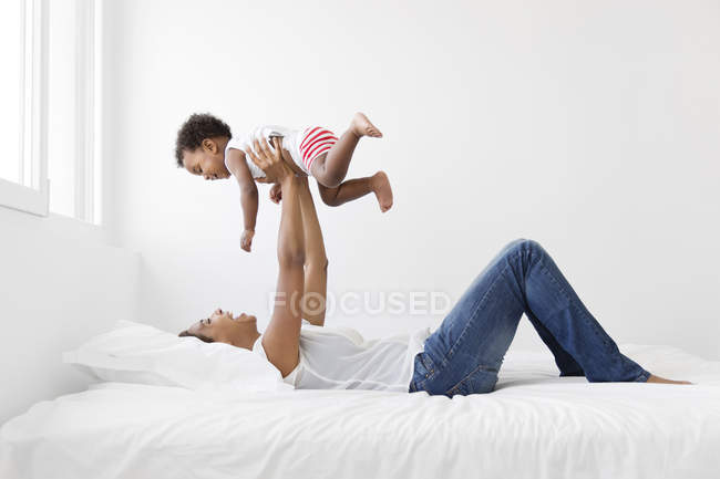 Woman lying on bed holding up baby — Stock Photo