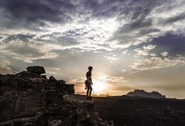 Alpinista in piedi sulla roccia — Foto stock