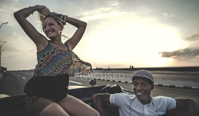 Man and woman riding in classic convertible car on top of seat back. — Stock Photo