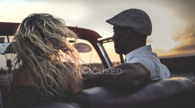 Man and woman riding in classic convertible car — Stock Photo