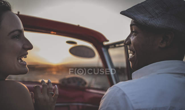 Man and woman riding in classic convertible car looking at each other. — Stock Photo