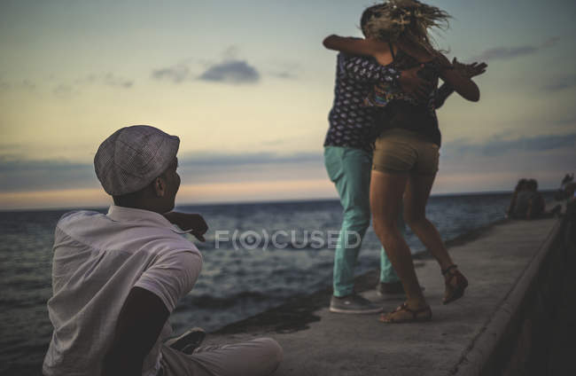 People dancing on seaside watched by man — Stock Photo