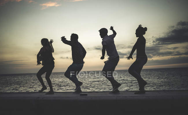 Four people dancing in line on sea wall background — Stock Photo