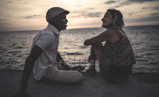 Two people sitting on seaside in front of ocean. — Stock Photo