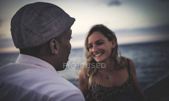 Two people facing each other in front of ocean. — Stock Photo