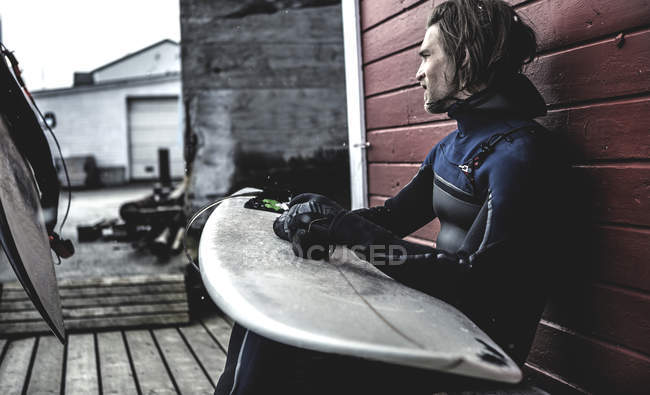 Surfer sitzt mit Surfbrett — Stockfoto