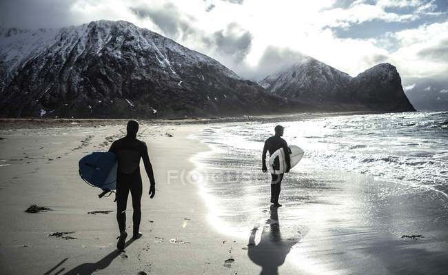 Surfers carrying surfboards — Stock Photo