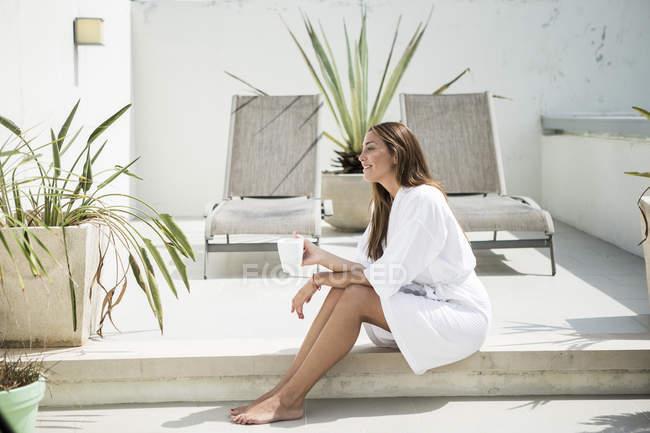 Woman in bathrobe sitting on terrace — Stock Photo