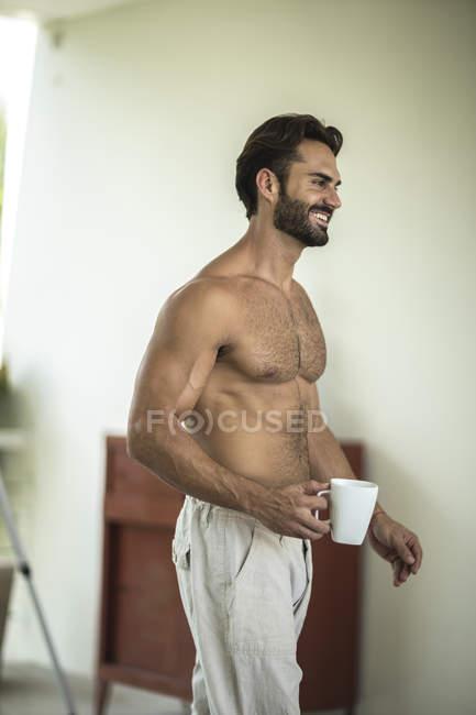 Man wearing sleepwear standing in bedroom. — Stock Photo