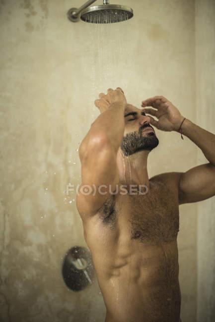 Чоловік, що стоїть в душ у ванній кімнаті. — стокове фото