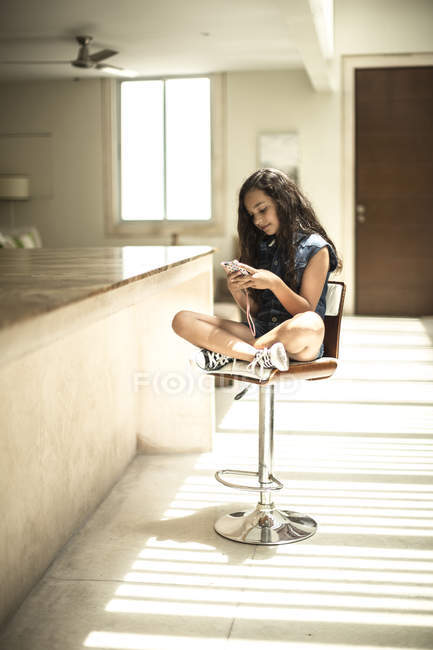 Jeune fille assise regardant téléphone mobile — Photo de stock