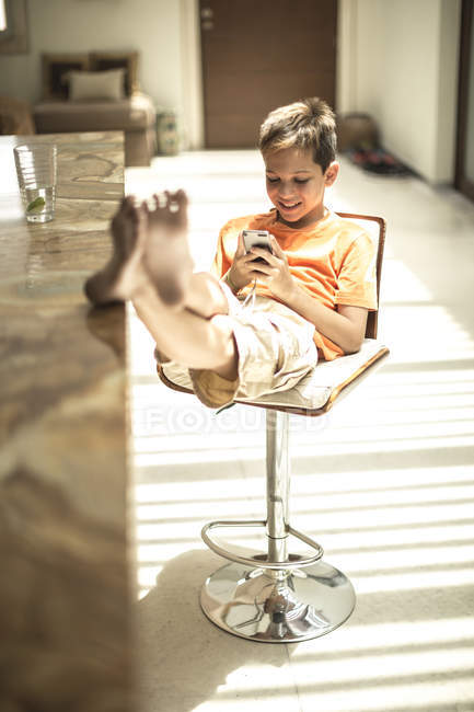 Boy sitting looking at mobile phone — Stock Photo