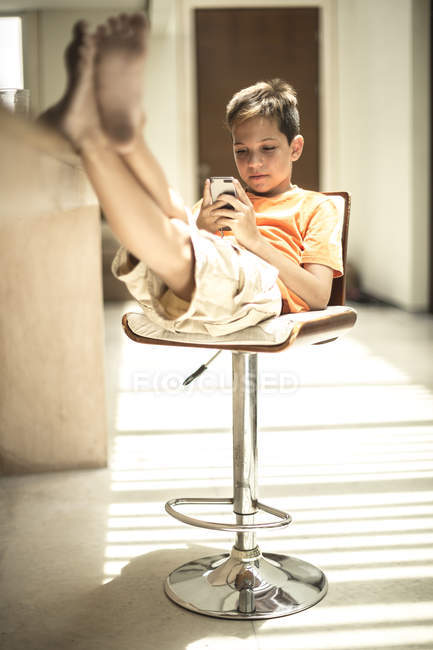 Мальчик сидит глядя на мобильный телефон — стоковое фото