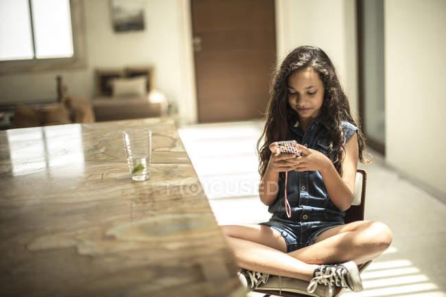 Девушка сидит глядя на мобильный телефон — стоковое фото
