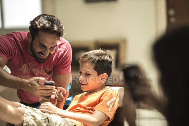 Man and boy looking at mobile phone — Stock Photo