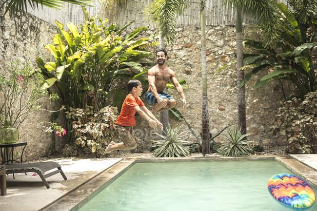 Uomo e ragazzo che salta nella piscina. — Foto stock