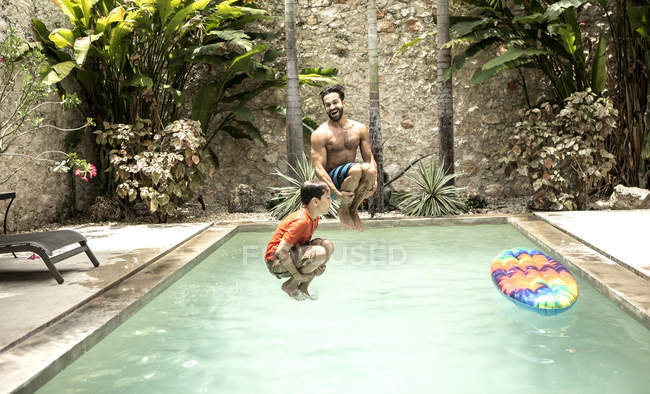 Man and boy jumping into swimming pool. — Stock Photo