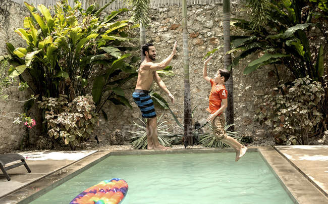 Человек и мальчик прыгает в бассейн — стоковое фото
