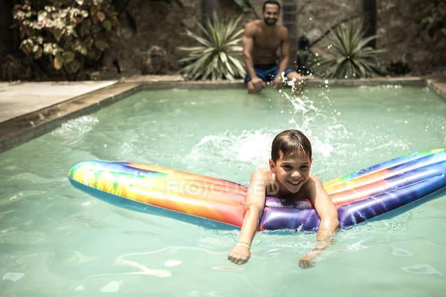 Мальчик плавает на плоту у бассейна — стоковое фото