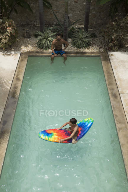 Мальчик сидит на плоту бассейн — стоковое фото