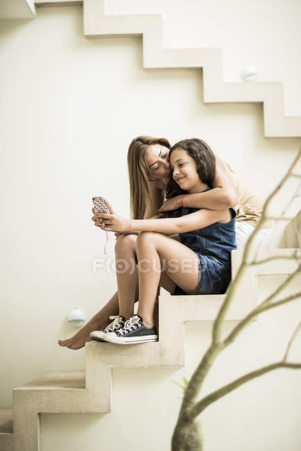 Woman and girl sitting on outdoor steps — Stock Photo