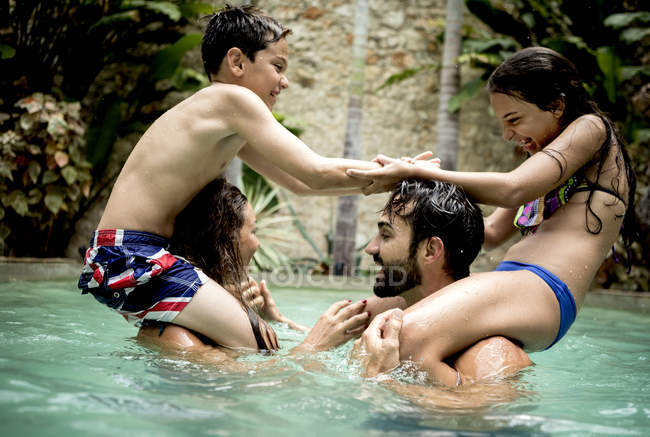 Children on shoulders of adults in swimming pool. — Stock Photo