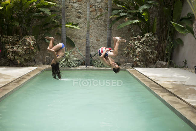 Children somersaulting into swimming pool. — Stock Photo