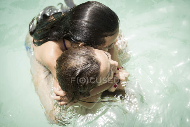 Woman and a girl hugging in swimming pool — Stock Photo