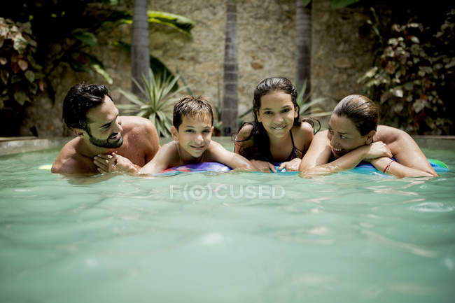 Family resting on pool raft — Stock Photo