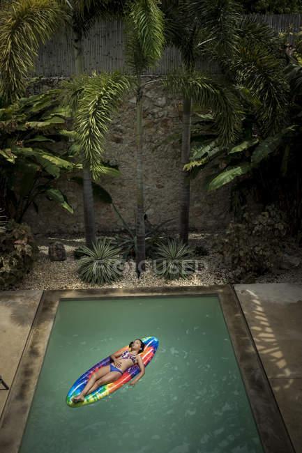 Girl lying on pool raft — Stock Photo