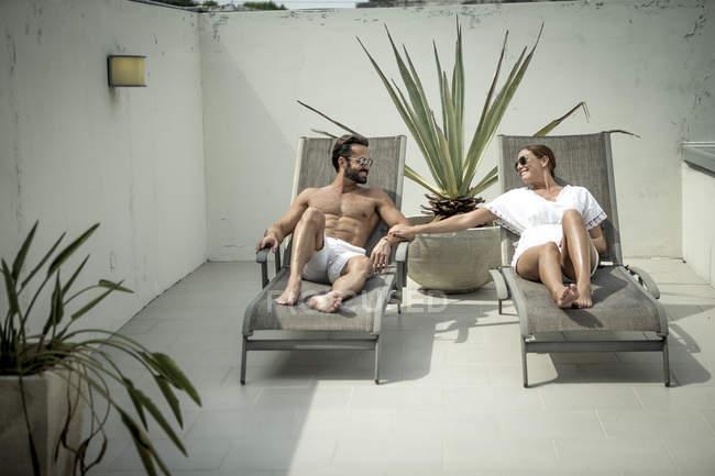 Couple lying on sun loungers — Stock Photo