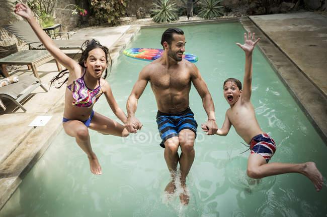 Uomo con i bambini che saltano nella piscina. — Foto stock